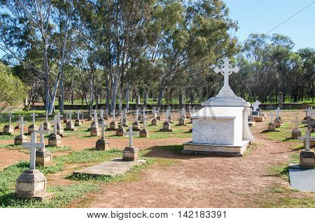 NEW NORCIA,WA,AUSTRALIA-JULY 15,2016: Old cemetery large upright monument surrounded by rows of headstones with crosses in peaceful treed landscape in the monastic town of New Norcia, Western Australia.