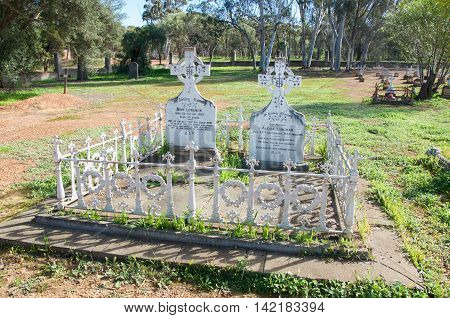 NEW NORCIA,WA,AUSTRALIA-JULY 15,2016: Old cemetery with fenced double plot in peaceful treed landscape in the monastic town of New Norcia, Western Australia.