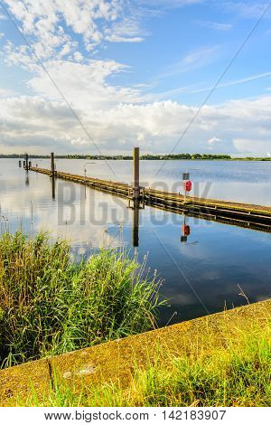 Long wooden jetty in a Dutch lake with a mirror smooth water surface and diagonally into the image. It is early in the morning on a beautiful windless summer day.