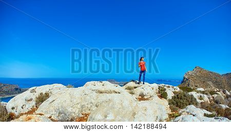 sporty female traveler with backpack standing on the cliff against sea and blue sky with white clouds at early morning, Crete, Greece.