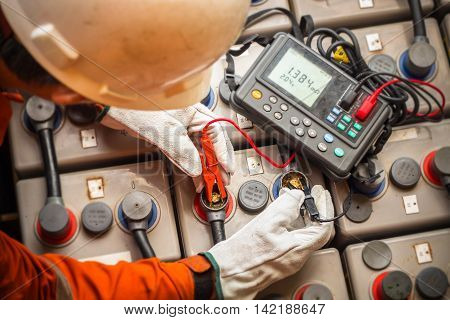 electrician using the digital battery tester to check the resistance and voltage of batteries