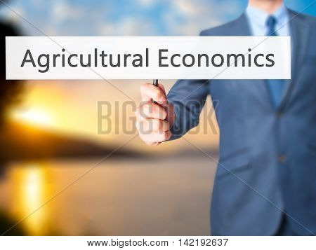 Agricultural Economics - Businessman Hand Holding Sign