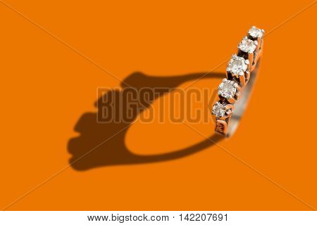 Diamond ring with shadow over an orange background
