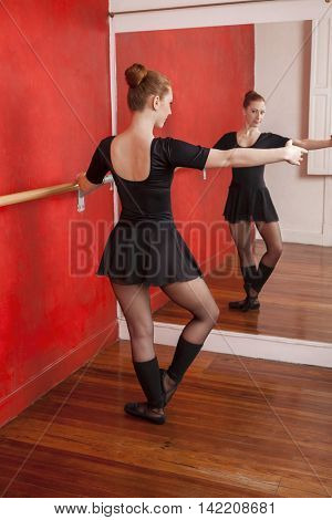 Female Ballet Dancer Practicing In Front Of Mirror