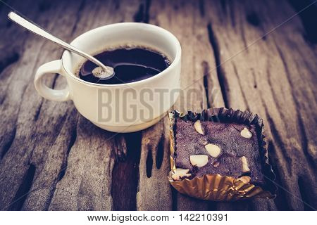 Piece of cake chocolate brownie and hot coffee on old wooden background. Shallow depth of field (dof) selective focus. High contrast and low key light picture style.