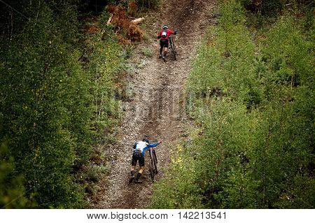 two athlete mountainbiker walking with bicycle uphill. extreme sports