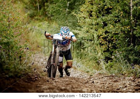 male athlete a cyclist walking uphill together with sport mountainbike
