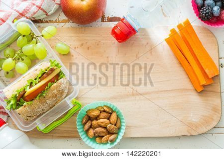 Making school lunch on wood background, top view