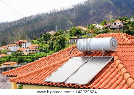 Water boiler with solar panels on roof of house in village of Madeira