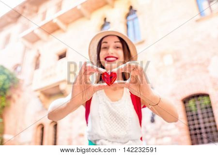 Beautiful woman holding decoration in the form of heart near Romeo and Juliet balcony in Verona. Romeo and Juliet is a romantic tragedy written by William Shakespeare