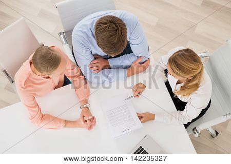 High Angle View Of Female Estate Agent Explaining Document To Young Couple