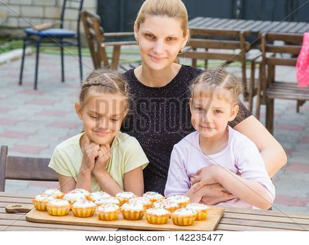 Mom And Two Daughters Sitting At A Table On Which Lay Cooked Them Easter Cupcakes