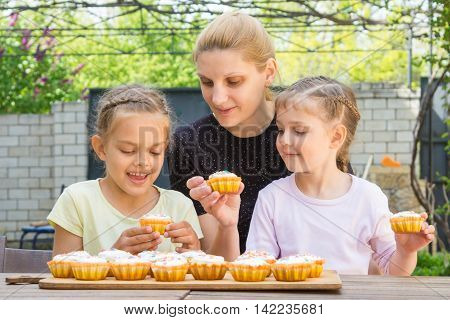 Mother And Two Daughters Sitting At The Table With Easter Cupcakes And They Are Risen