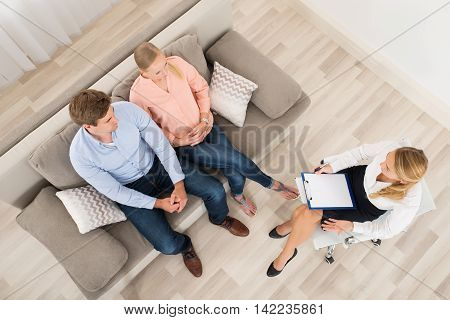 Elevated View Of A Couple Sitting On Sofa With Psychologist Holding Clipboard