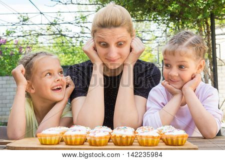 Mother And Two Daughters Having Fun And Looking At Easter Cupcakes