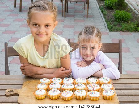 Two Sisters Sitting At A Table On Which Are Freshly Baked Easter Cupcakes