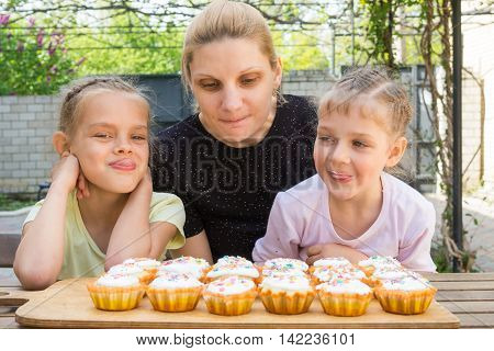 Mother And Two Daughters Salivate Looking At Freshly Easter Cupcakes