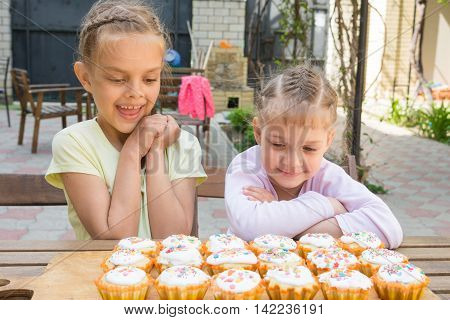 Two Sisters With An Appetite For Looking At Home-baked Easter Cakes