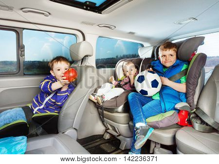 Three little boys, age-diverse brothers, travelling by car in safety seats, snacking and playing ball during the trip