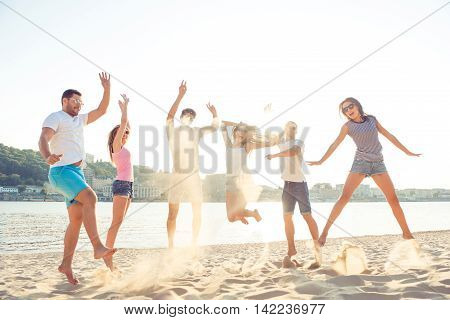 Outing Near Waterfront,  Joyful Girlfriends With Boyfriends Jumping At Summertime Sunset In Shorts A