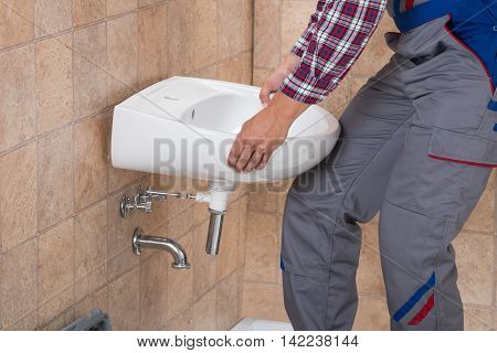 Close-up Of Young Handyman Installing Sink In Bathroom