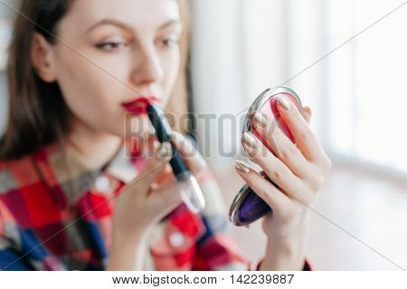 A beautiful young woman applying her make-up in the mirror