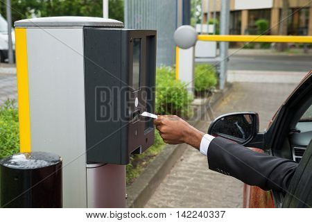 Person Sitting In Car Using Parking Machine To Pay For Parking