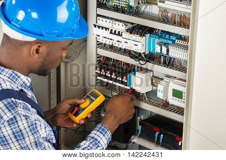 Close-up Of Male Electrician Checking Fuse Box With Multimeter poster