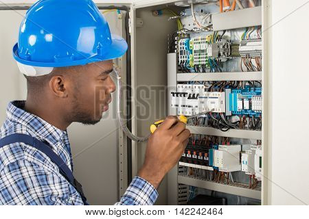 Close-up Of Young Male Technician Examining Fusebox With Screwdriver