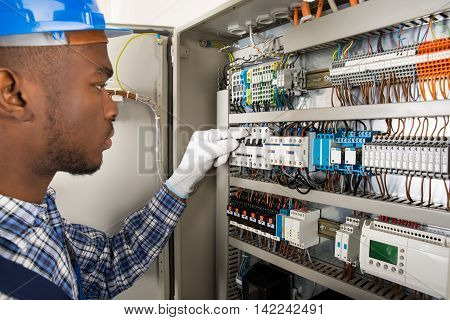 Photo Of Young African Male Technician Checking Fusebox