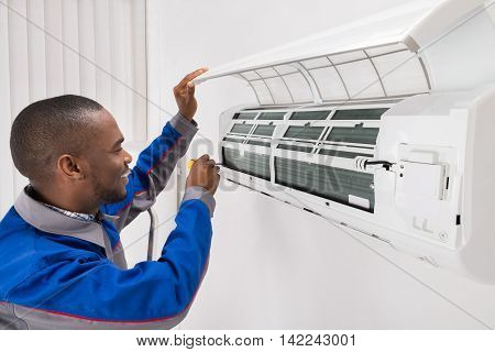 Happy Young African Male Technician Repairing Air Conditioner poster