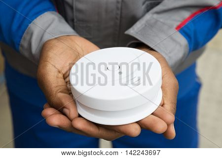 Close-up Of Electrician Hands Holding Smoke Detector