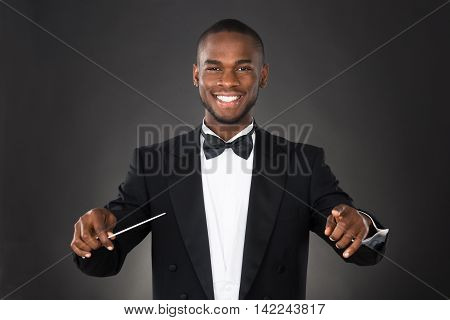 Portrait Of Happy Music Conductor With Baton Against Black Background