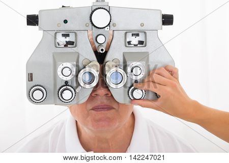 Close-up Of An Optometrist's Hand Adjusting Phoropter For Senior Male Patient