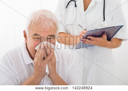 Senior Man Infected With Cold Blowing His Nose While Doctor Writing On Clipboard In Clinic