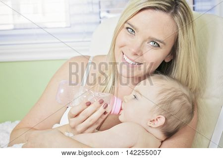 Young mother at home feeding their new baby girl with a milk bottle, feeling proud, joyful and fulfilled. Close up portrait being together.