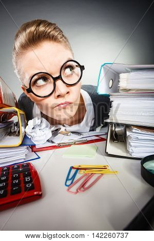 Facial expressions during work. Crazy thoughtful accountant businesswoman surrounded by documents and binders in office.