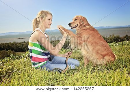 Teenage girl plays with the dog outside. The dog give his foot.