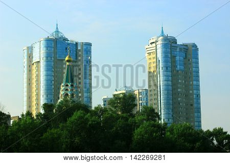 tower high-rise residential buildings and the dome of the Church on a background of green foliage of tree crowns