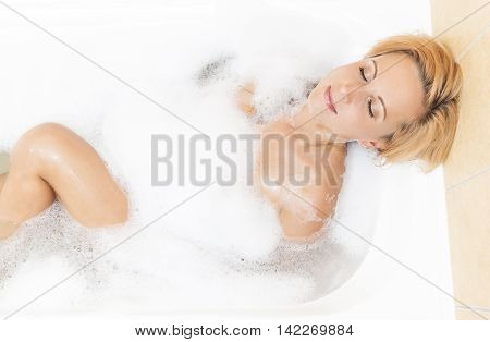 Spa and Welness Concepts and Ideas. Sensual Caucasian Blond Woman Relaxing In Bathtub with Bubble Foam. Horizontal Image Composition