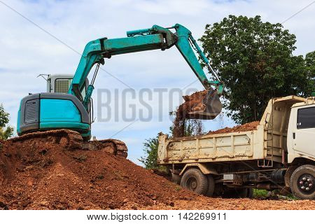 Industrial loader excavator moving earth and unloading on a dumper truck