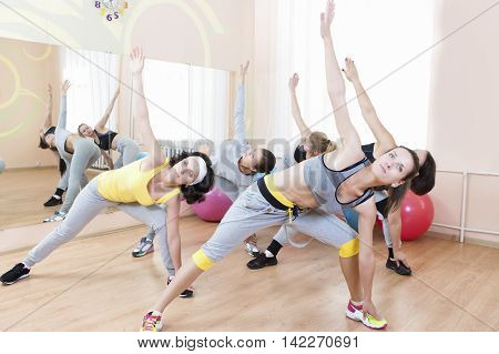Sport Concepts. Group of Five Young Caucasian Females Making Stretching Exercises in Sport Venue. Horizontal Image Orientation