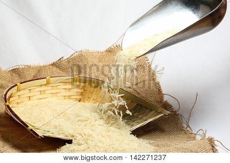 White long grain rice on jute bag and bamboo pot metal scoop