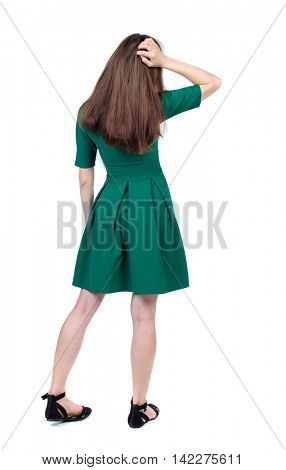 back view of standing young beautiful  woman.  girl  watching. Rear view people collection.  backside view of person. The slender brunette in a green short dress thoughtfully scratching his head.