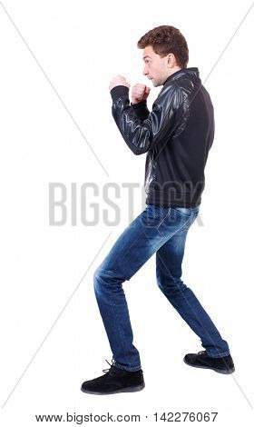 back view of guy funny fights waving his arms and legs. Isolated over white background. Rear view people collection.  backside view of person.Curly guy in a black leather jacket in a fight.