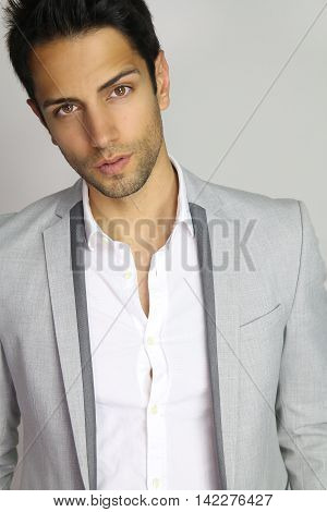 handsome male wearing a gray suit over a white background