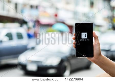 CHIANG MAITHAILAND - JULY 17 2016 : A man hand holding Uber app showing on LG G4 on road and red car Uber is smartphone app-based transportation network.