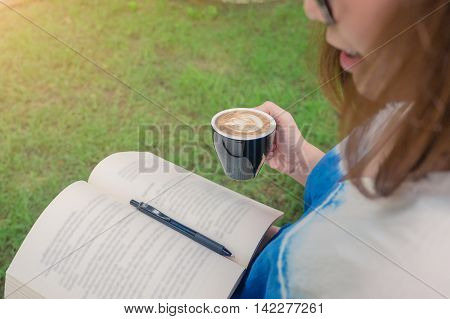 Cute lovely young woman reading book and drinking coffee at outdoor park. focus on hand holding cup of coffee.