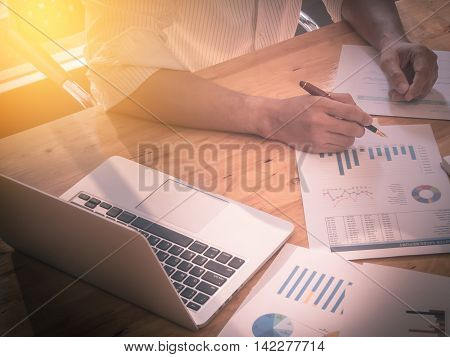 close up of business man hand holding pen for working on laptop computer with business graph information diagram on wooden desk. vintage effect.