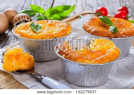 Three portions of French julienne. Mushroom chicken and cheese gratin in Mini Baking cups decorated with basil leaves on old rustic boardsOne-Bite on spoon authentic recipe top view close-up